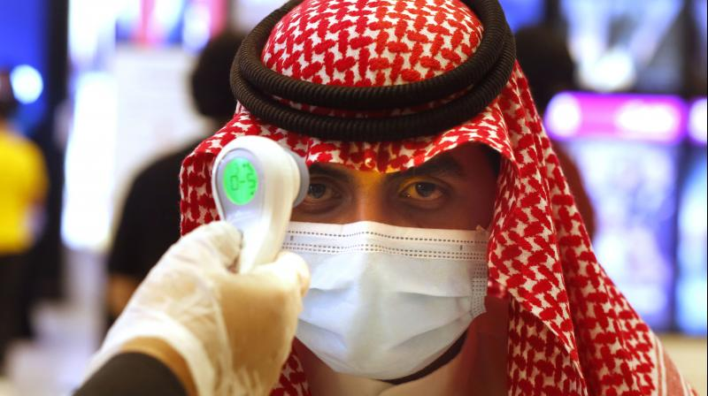 A Saudi cinema viewer has his temperature taken as he wears a face mask to help curb the spread of the coronavirus. (AP)