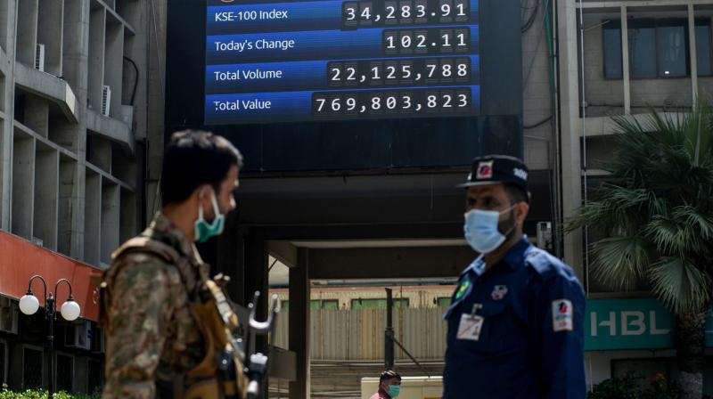 A paramilitary soldier (L) stands guard next to a board showing KSE-100 Index information at the Pakistan Stock Exchange a day after a gunmen attack in Karachi on June 30, 2020. (AFP)