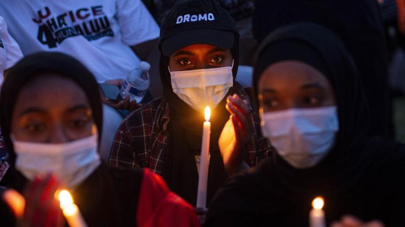 eople gather for a candlelight vigil in memory of musician and activist Hachalu Hundessa at the Oromo Community of Minnesota building on June 30, 2020 in St Paul, Minnesota. (AFP)