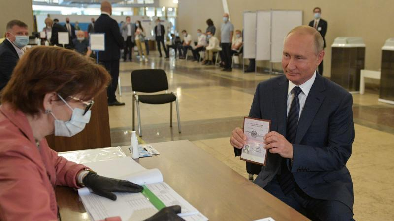Russian President Vladimir Putin shows his passport to a member of a local electoral commission as he arrives to cast his ballot in a nationwide vote on constitutional reforms at a polling station in Moscow on July 1, 2020. (AFP)