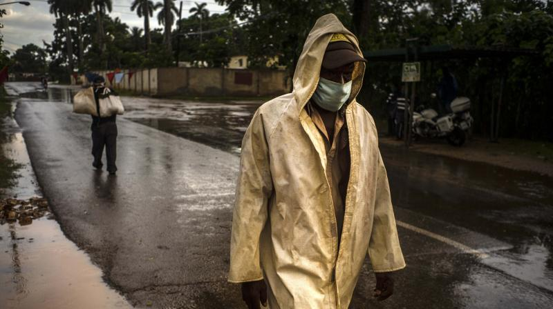 A man wearing a protective face mask as a precaution against the spread of the new coronavirus walks along a street after a shower. (AP)