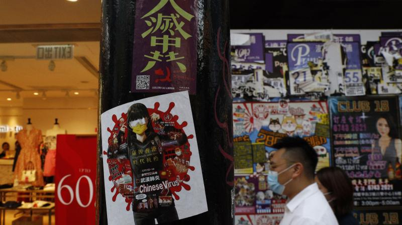 A man walks past the stickers with messages about an anti-Beijing government are left by protesters on a street in Hong Kong, Thursday, July 2, 2020. (AP)