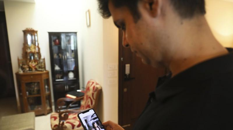 Karan Murgai, an IT management consultant for a multinational based in Dallas, shows on his phone in New Delhi, India, photograph of his daughters, who are in Dallas. (AP)