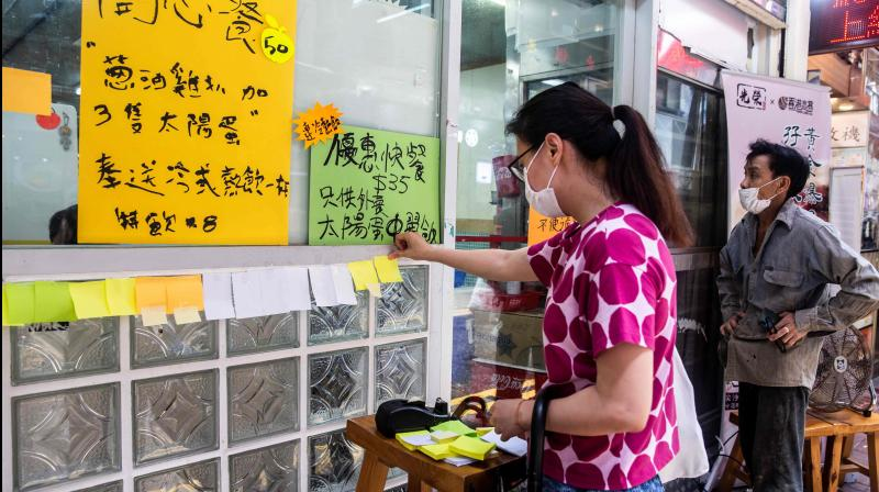 "A woman (L) sticks a blank note onto a ""Lennon Wall"" outside a pro-democracy restaurant in Hong Kong on July 3, 2020, in response to a new national security law introduced in the city which makes political views, slogans and signs advocating Hong Kong's independence or liberation illegal. (AFP)"