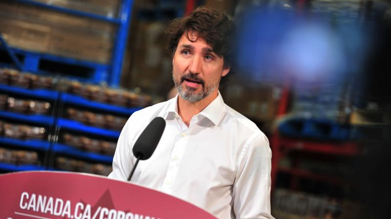 Canadian Prime Minister Justin Trudeau speaks to the press as he volunteers at the Moisson Outaouais food bank in Gatineau, Quebec, Canada. (AFP)