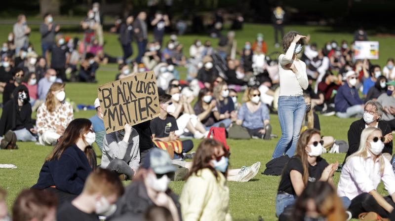People maintain physical distances as thousands gather at a rally supporting the Black Lives Matter and Black Deaths in Custody movements in Sydney. (AP)