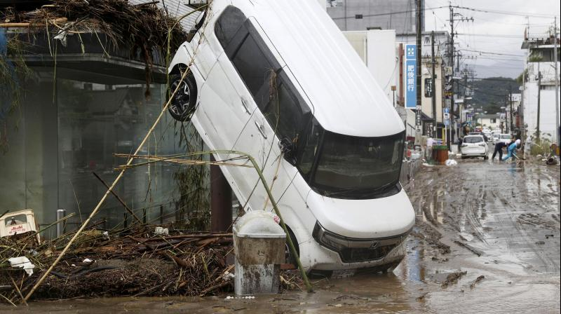 A car leans against a building following a heavy rain in Hitoyoshi, Kumamoto prefecture, southern Japan Monday, July 6, 2020. (AP)