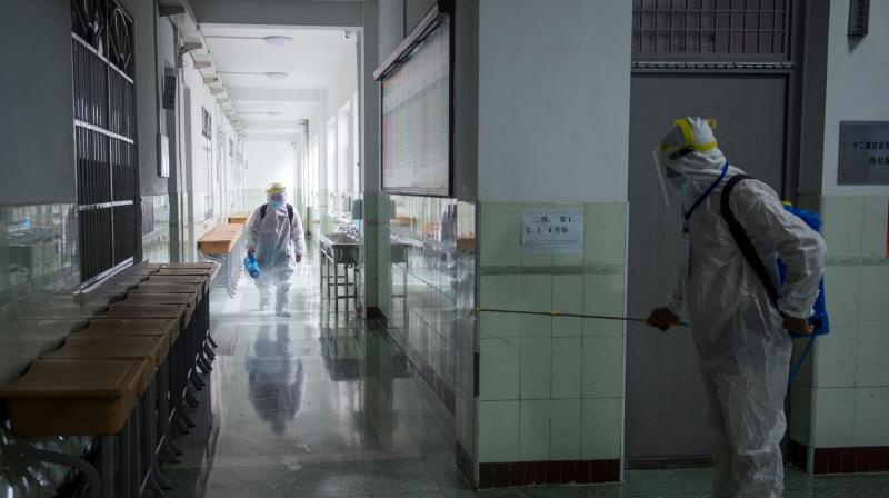 This photo taken on July 5, 2020 shows staff members wearing protective clothing spraying disinfectant in the compounds of a school ahead of the National College Entrance Examination (NCEE), known as Gaokao, in Wuhan in China's central Hubei province. (AFP)