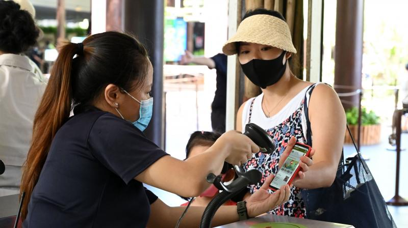 A staff scan the e-ticket of a visitor at the Singapore Zoo in Singapore on July 6, 2020, on its first day of reopening to the public after the attraction was temporarily closed due to concerns about the COVID-19 novel coronavirus. (AFP)