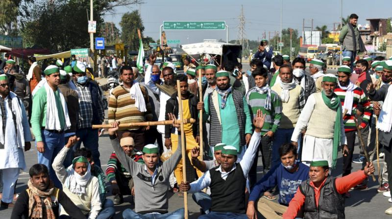 Farmers stage a protest on the national highway over farm reform laws, in Bulandshahr. (PTI)