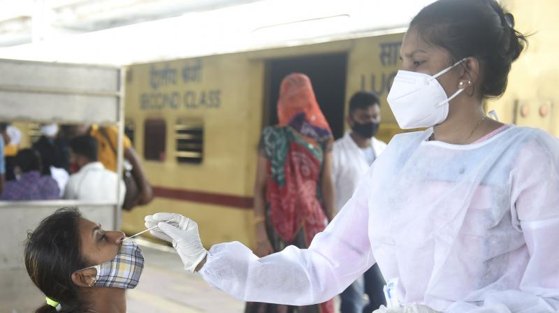 A BMC health worker collects swab sample of a passenger for COVID-19 testing, at Dadar railway station in Mumbai on June 22, 2021. (PTI/Shashank Parade)