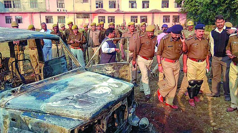 Policemen inspect the area where several vehicles were set on fire by a mob during a protest over the alleged illegal slaughter of cattle in Bulandshahr. (Photo: PTI)