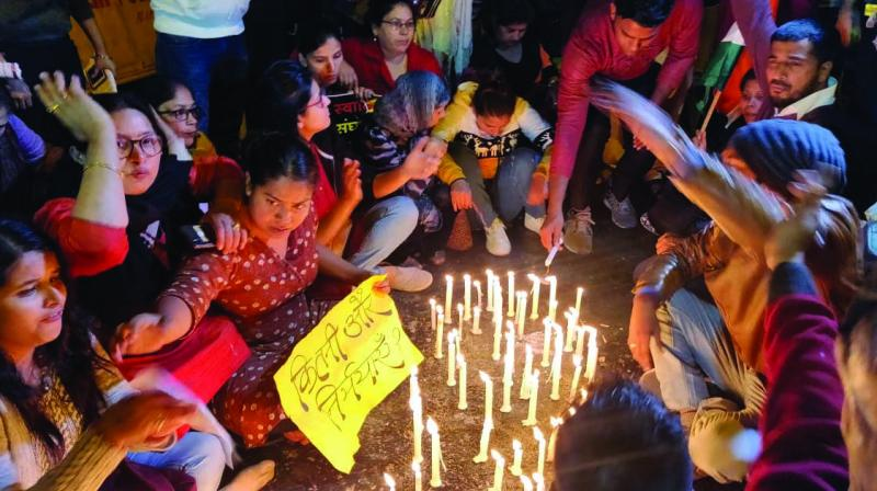 Women light candles in memory of rape victims in New Delhi on Saturday. (Photo: PTI)