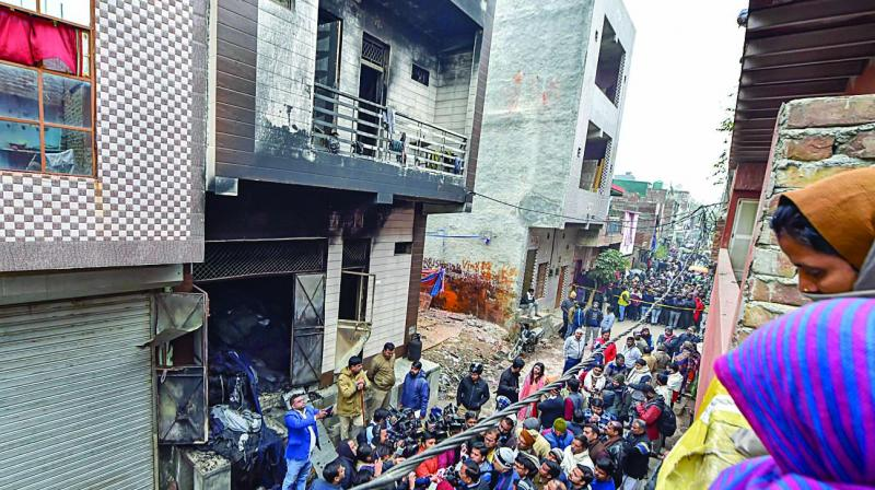 Neighbours look at the damaged three-storey building, on Monday. (Photo: PTI)