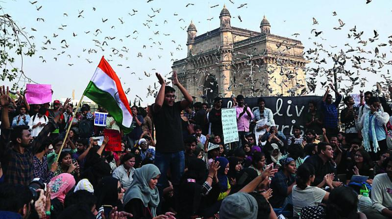 Pigeons fly near the Gateway of India as students participate in a protest against Sunday's assault by masked assailants at New Delh's Jawaharlal Nehru University in Mumbai on Monday. (Photo: AP)