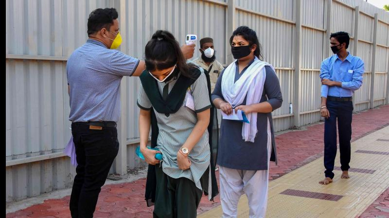 Students wearing protective masks undergo thermal screening before appearing in the higher secondary school examinations of Madhya Pradesh Board of Secondary Education, during the fifth phase of ongoing COVID-19 lockdown, in Bhopal. PTI photo