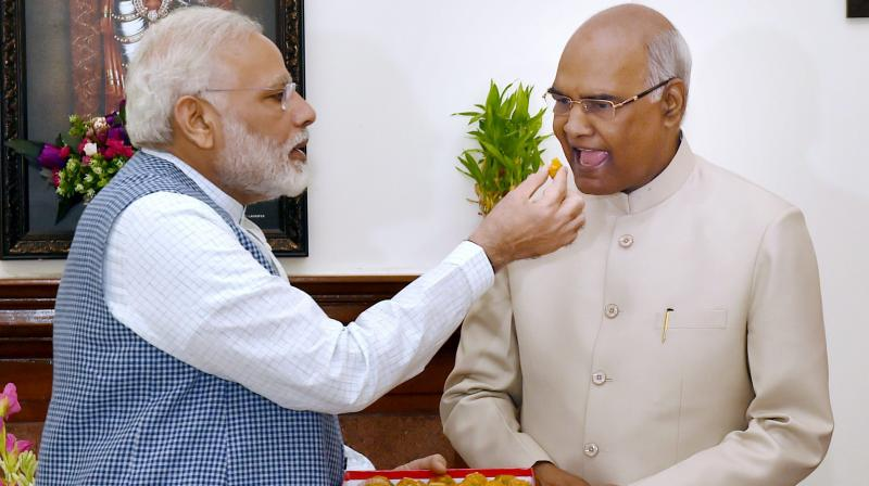 Prime Minister Narendra Modi offers sweet to Ram Nath Kovind on being elected as the 14th President of India, in New Delhi. (Photo: PTI)