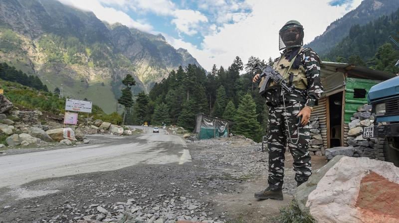 A security personnel stands guard along the Srinagar-Ladakh Highway, at Gagangir in Ganderbal District of Central Kashmir. PTI Photo
