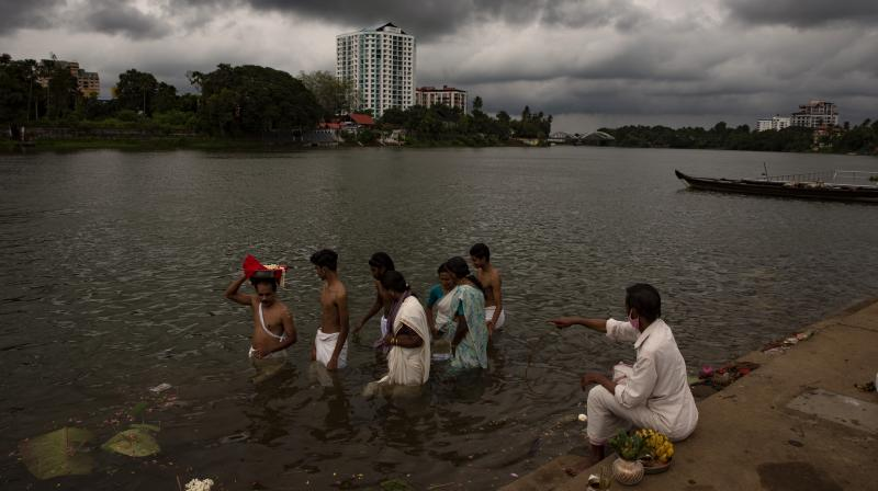 A man wearing a mask as a precaution against the coronavirus sits and guides as a Hindu family performs the last rites of a deceased relative on the banks of the Periyar river in Kochi, Kerala. (AP file photo)