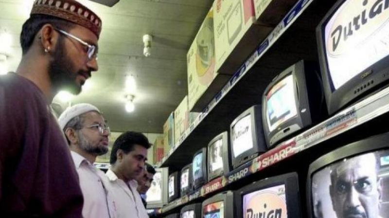 People watch TV programes in Karachi. (Photo: AFP)