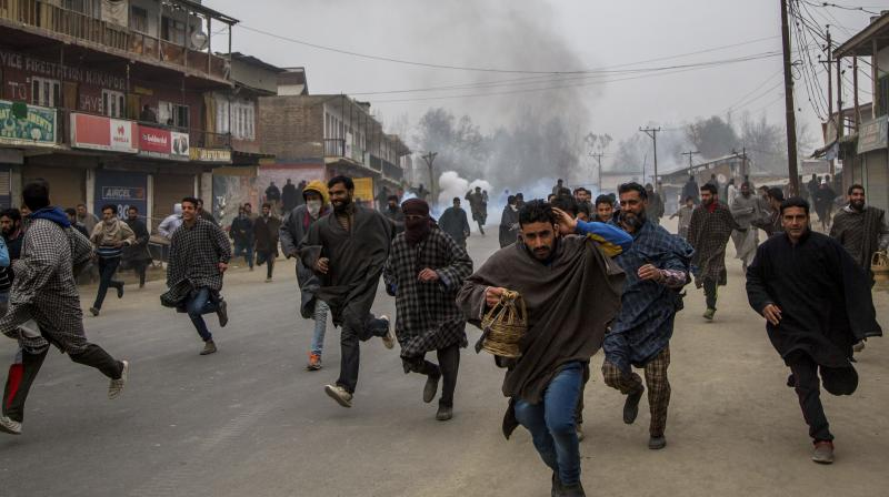 Kashmiri villagers run for cover from tear gas shells and pellets fired at them by Indian police during a protest near the funeral of Rayees Ahmad Dar, a suspected militant of Lashkar-e-Taiba (LeT) in Kakpora village south of Srinagar. (Photo: AP)