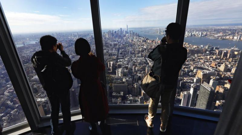 Workers mounted metal baskets suspended outside the 103rd floor, wearing harnesses attached to the building. (Photo: AP)