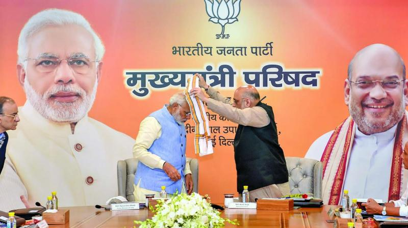 Prime Minister Narendra Modi is welcomed by BJP president Amit Shah during a day-long meeting of the BJP chief ministers in New Delhi on Tuesday. (Photo: PTI)