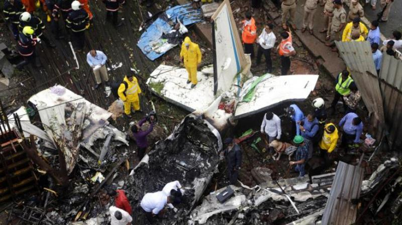 Rescuers stand amid the wreckage of a private chartered plane that crashed in Ghatkopar area, Mumbai. The plane hit an open area at a construction site for a multistory building in a crowded area with many residential apartments. 5 people including one on the ground were killed. (Photo: AP)