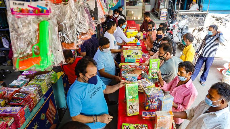 People buy firecrackers despite the government urging public to restrain from bursting crackers during Diwali festival in view of current COVID-19 status, in Thane district, Monday, Nov. 9, 2020. (PTI)