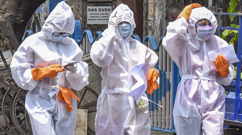 Health workers wearing protective suits go on a door to door survey in Kolkata. PTI photo