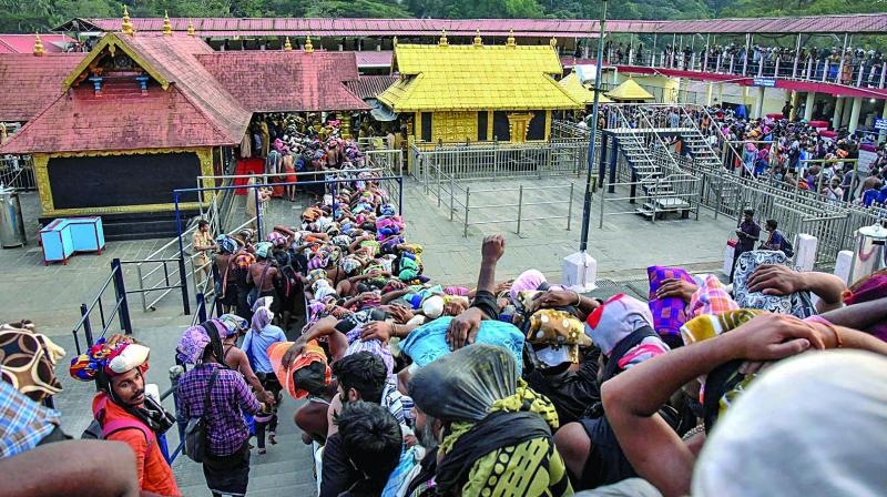 """Devotees arrive at the Sabarimala temple in Kerala's Pathanamthitta district on Monday. This is the second time the hill shrine opened for """"darshan"""" after the Supreme Court allowed the entry of women of all age groups. (Photo: PTI)"""