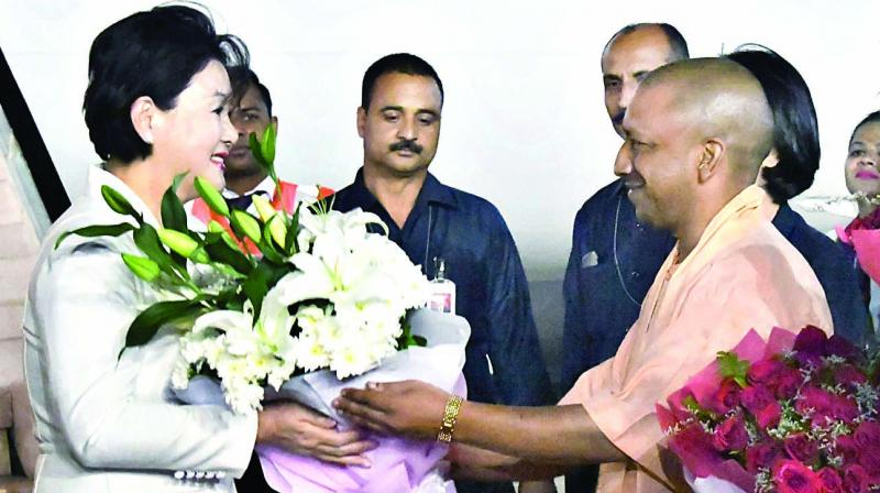 Uttar Pradesh chief minister Yogi Adityanath presents a bouquet to South Korean first lady Kim Jung-sook at the Chaudhary Charan Singh airport in Lucknow on Monday. (Photo: PTI)