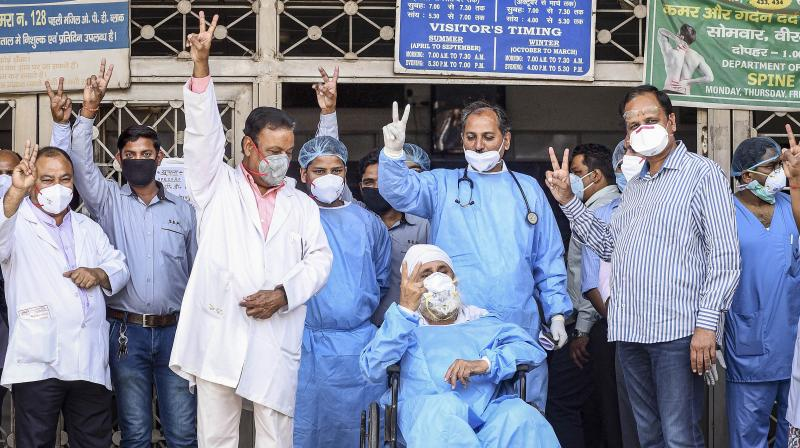 Eighty-two-year-old Manmohan Singh, in a wheelchair, comes out from the Lok Nayak Jai Prakash Narayan (LJNP) Hospital in New Delhi on Tueday amid cheers from doctors and medical staff after he fully recovered from Covid-19. The elderly are among the most vulnerable groups. (PTI)