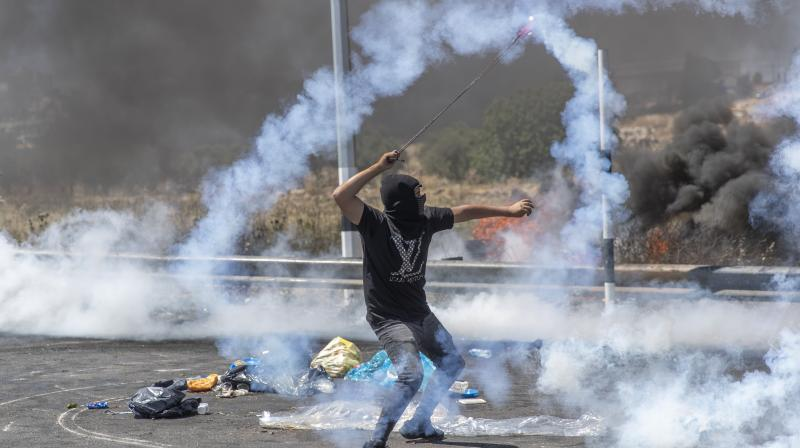 A Palestinian demonstrator uses a slingshot to return a teargas canister toward soldiers during clashes with Israeli troops at the northern entrance of the West Bank city of Ramallah. (AP)