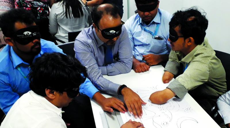 People with and without special needs experiencing a tactile art with blindfolds on as part of disability awareness session conducted by Access For All for Standard Chartered bank.