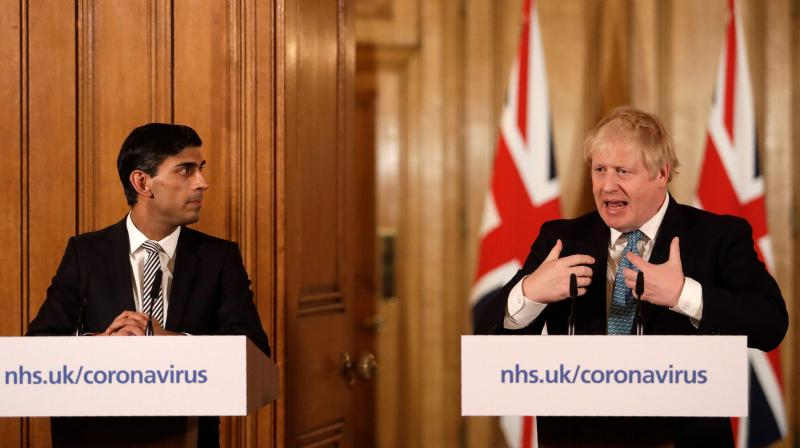 Britain's Chancellor of the Exchequer Rishi Sunak (L) and Britain's Prime Minister Boris Johnson (R) attend a news conference addressing the government's response to the novel coronavirus COVID-19 outbreak, inside 10 Downing Street in London. AFP Photo