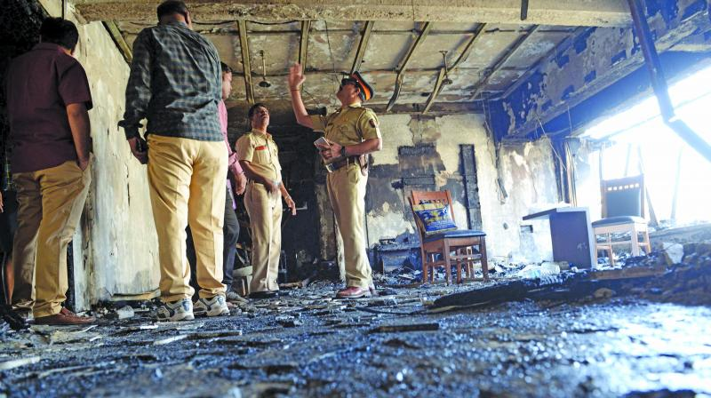 Cops inspect the gutted flat on the 11th floor of the Sargam Housing Society on Friday. (Photo: Rajesh Jadhav)
