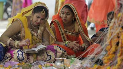 Married women, dressed in their finery, perform rituals under a Banyan tree on the occassion of Vat Savitri. (Photo: AP/Ajit Solanki)