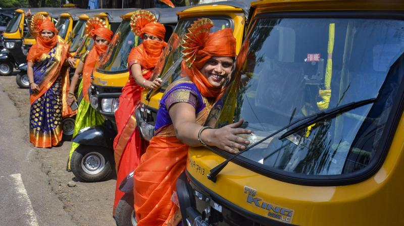 Women, who were given free training, pose for photographs in front of auto rickshaws distributed by Shiv Sena Women Cell, at Pachpakhadi in Thane district. — PTI photo