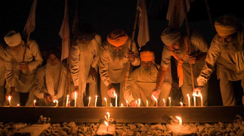 Farmers light candles in support of the Haryana farmers organisations as they announced to protests against three farm laws on the outskirts of Amritsar. — PTI photo