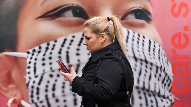 A pedestrian walks past a poster of a person wearing a face covering, in the high street in west London. — AFP photo