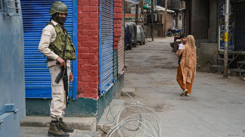 A security personnel stands guard amidst total lockdown imposed in the valley after a surge in COVID cases in Sringar. PTI photo
