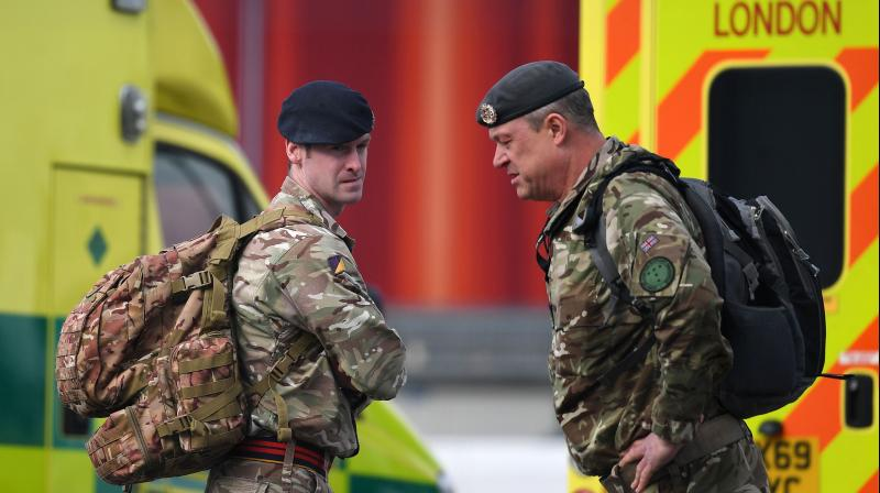 Members of Britain's armed forces stand by London Ambulances in a car park at the ExCeL London exhibition centre in London. AFP Photo