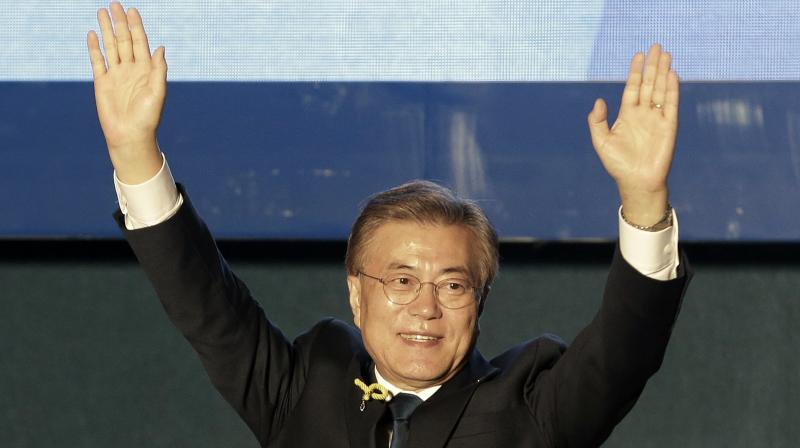 South Korea's presidential candidate Moon Jae-in of the Democratic Party raises his hands as he arrives to give a speech on a stage in Seoul. (Photo: AP)