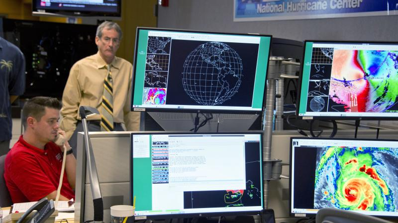 Hurricane Specialist Robbie Berg, left, and Ed Rappaport, right, the acting director of the National Hurricane Center, participate in a coordinating conference call for a Hurricane Irma forecast package Saturday. (Photo: AP)