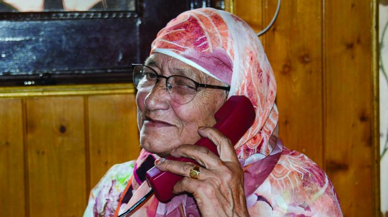 An elderly resident talks on phone after authorities in Kashmir restored 19 more telephone exchanges, a month after telephone services were snapped following abrogation of provisions of Article 370, in Srinagar on Thursday. (Photo: PTI)