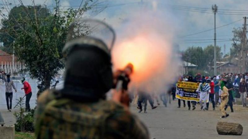 A policeman fires teargas shells to disperse protesters during a clash, which erupted after Id prayers, in Srinagar. (Photo: PTI)