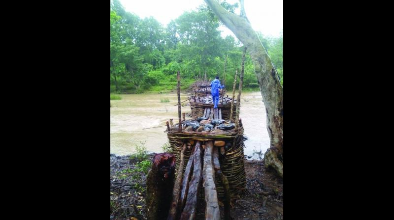 The bridge is made of bamboo, huge wooden logs and stones.