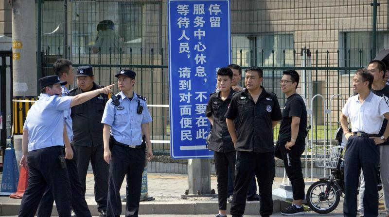 Chinese security personnel stand outside the US Embassy, in the background, after a reported blast occurred nearby in Beijing. (Photo: AP)