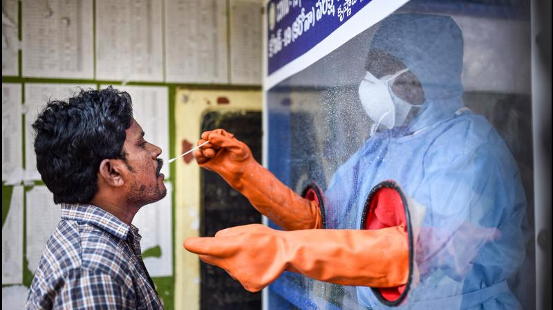 A health worker collects a swab sample of a man for Covid19 test in a swab collection booth in Vijawayada. PTI Photo